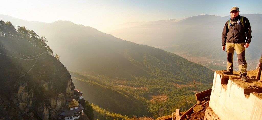 Man standing on the edge of a hill in Bhutan with mountains behind