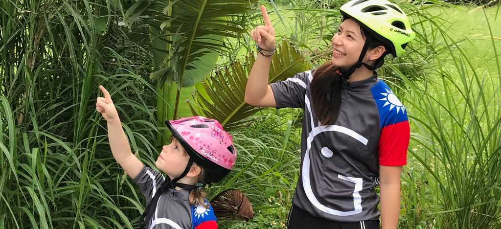 Young girl and woman pointing at something wearing Grasshopper Adventures Taiwan cycling jerseys