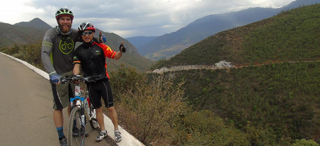 Trip leader and guide in jersey in front of mountains in China with bicycle