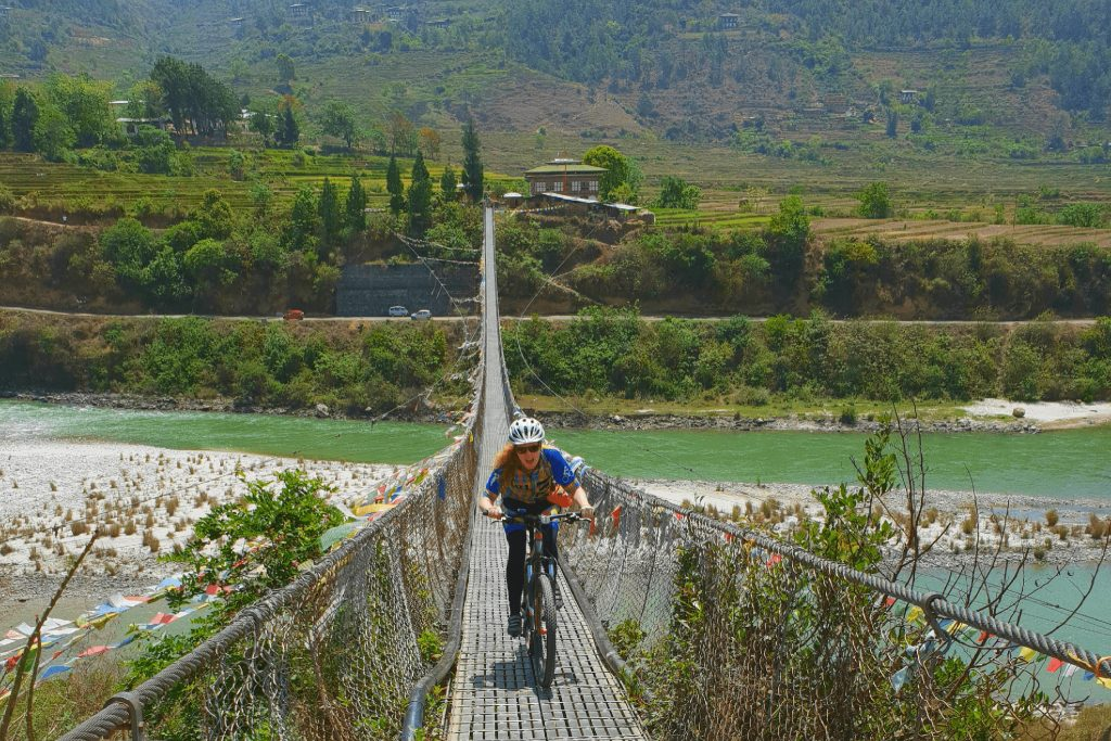 Cyclist riding on bridge over river in Bhutan