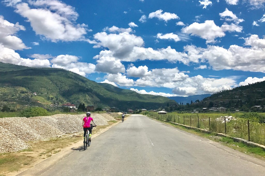 Cyclists riding on concrete road with clody sky and mountains in the distance