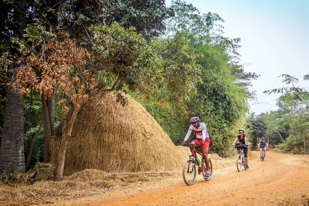 Countryside in Cambodia - cyclists passing a haystack