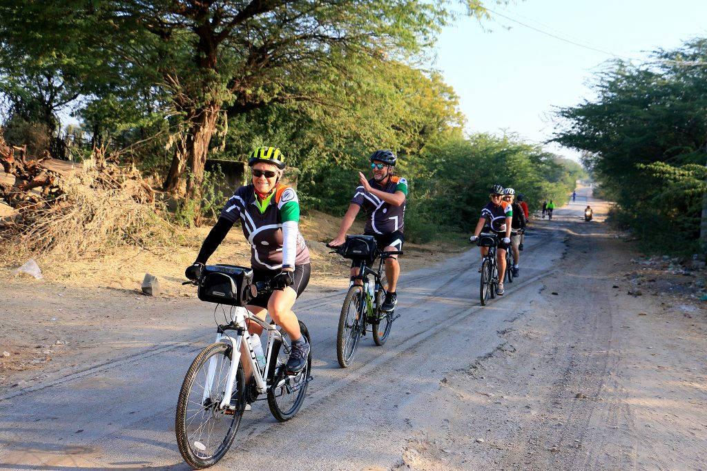 Cyclists riding on tree lined road in India