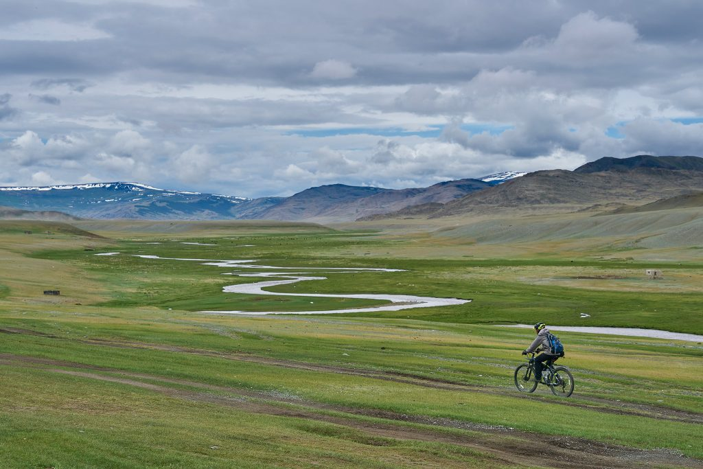 Cyclist riding through the Mongolian plains