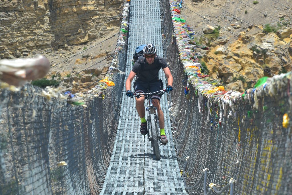Male cyclist riding on bridge