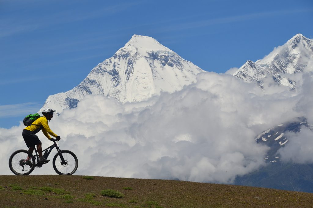 Cyclist riding past clouds and white peaks of the Himalayas
