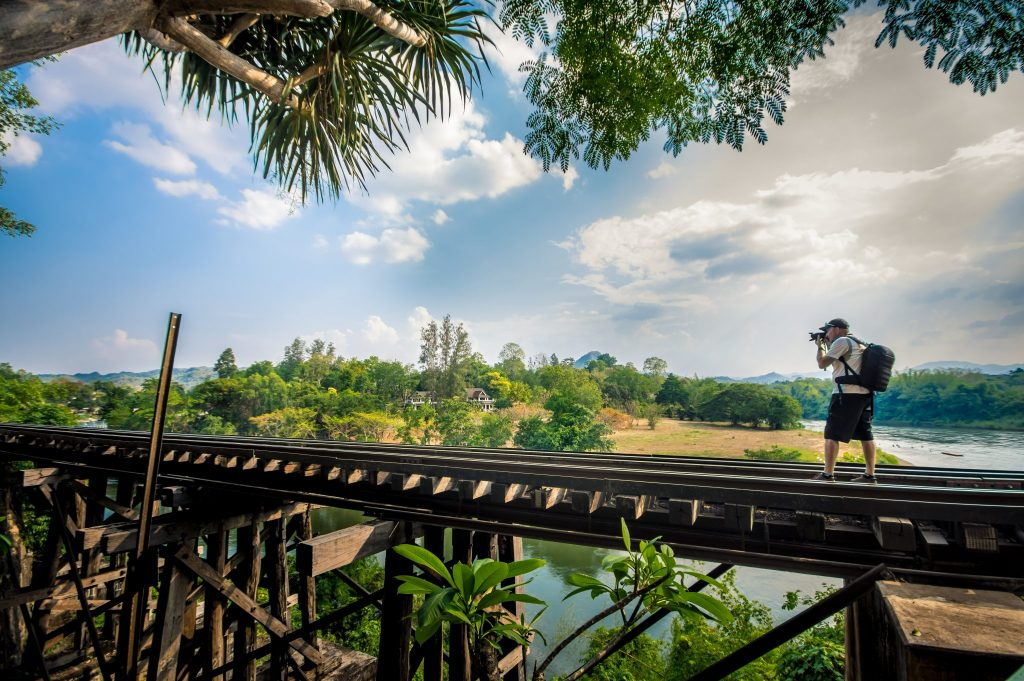 Tourist taking a photo on the railway trestle in Kanchanaburi, Thailand