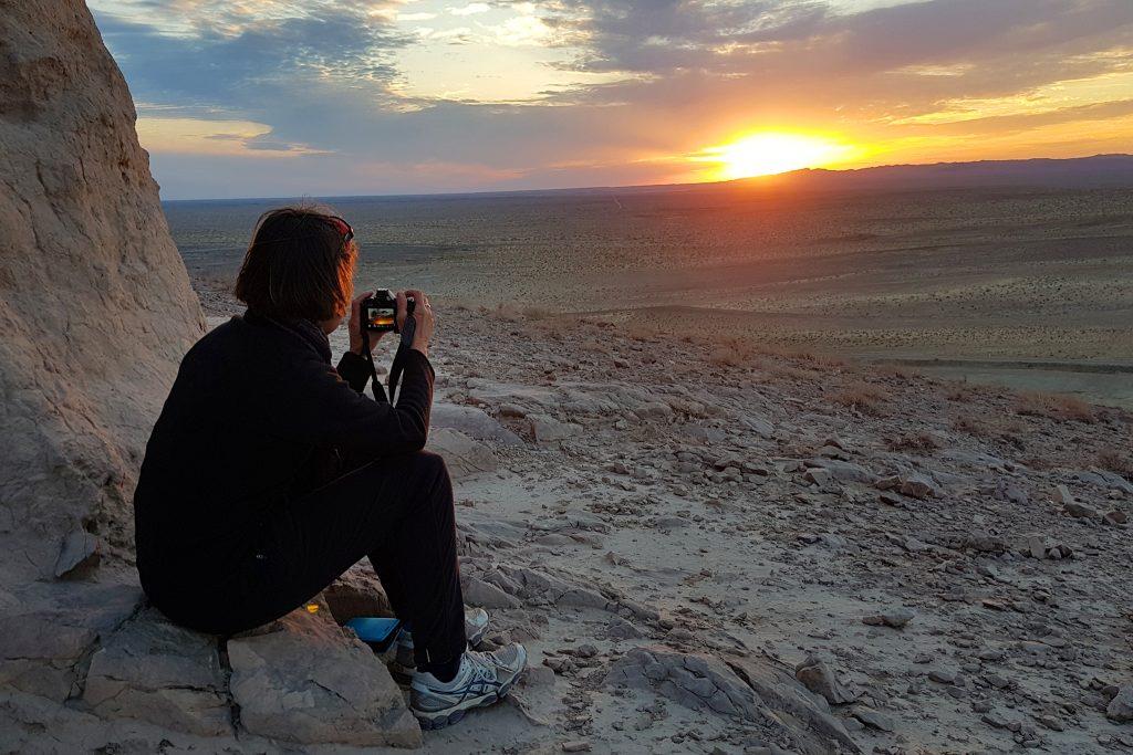 Woman tourist taking photo of sunset