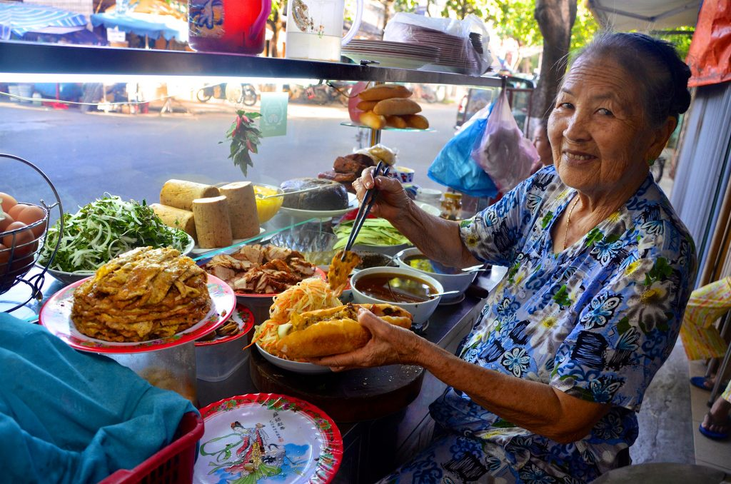 Local woman making street food sandwich in Vietnam
