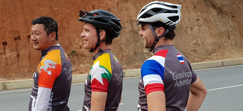 Three men in cycling jerseys, one Bhutan jersey, one Myanmar, one Thailand