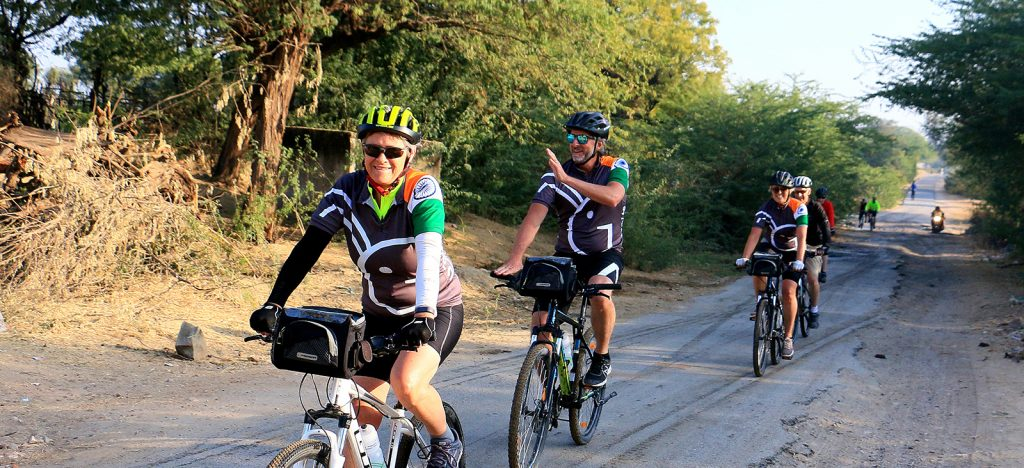 Cyclists riding concrete path wearing Grasshopper Adventures India cycling jerseys