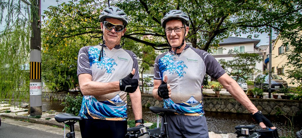 Two men cyclists in helmets giving the thumbs up in Grasshopper Adventures Japan cycling jerseys