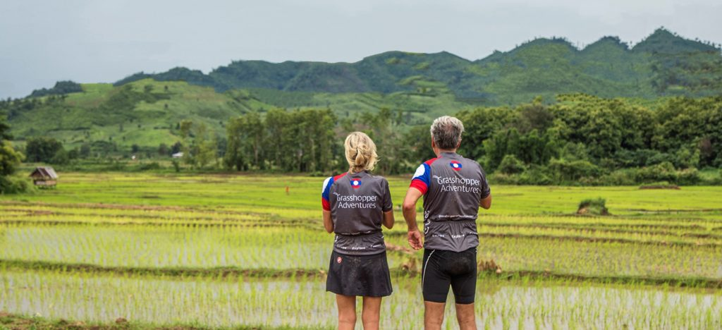 Two cyclists in Laos Grasshopper Adventure jerseys looking at green views