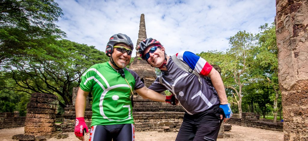 Two cyclists in Thailand Grasshopper Adventures jersey