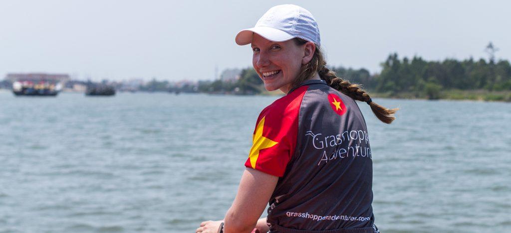 Smiling female cyclist in Vietnam Grasshopper Adventures jersey