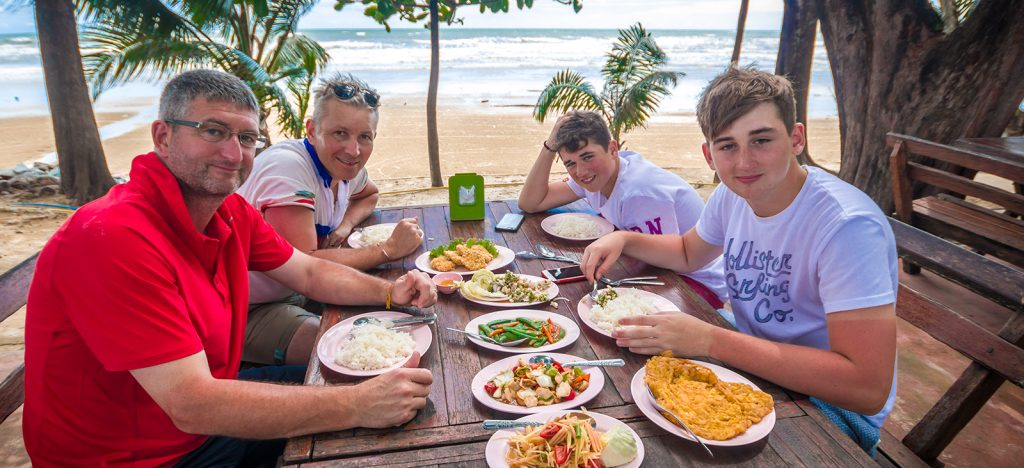 Two adults and two young boys eating traditional meal on the beach