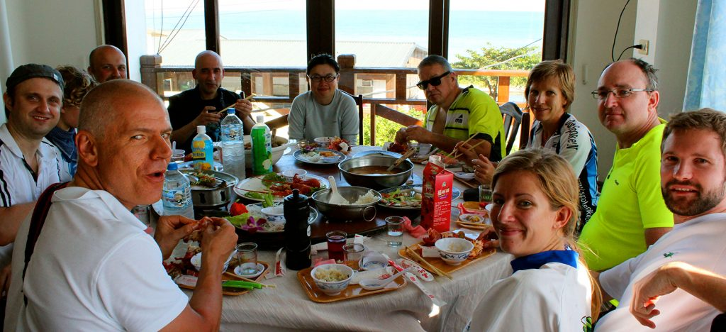 Group of travelers around the table eating traditional Taiwanese food