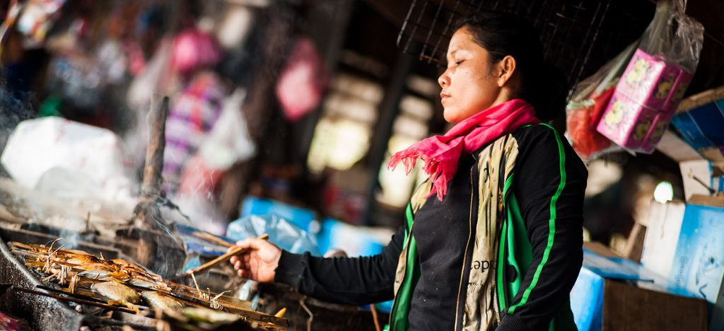 Cambodian woman grilling meat and fish over fire