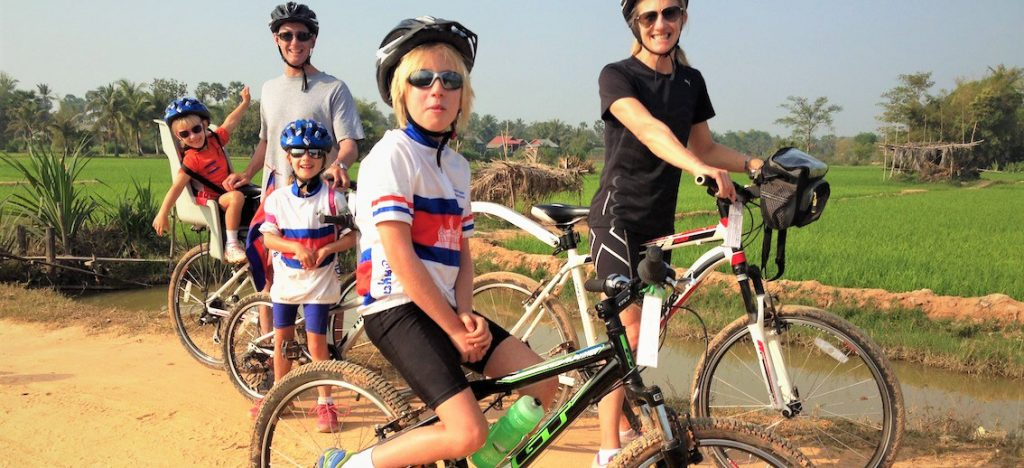 Family with three children on bikes in front of rice paddies in Cambodia