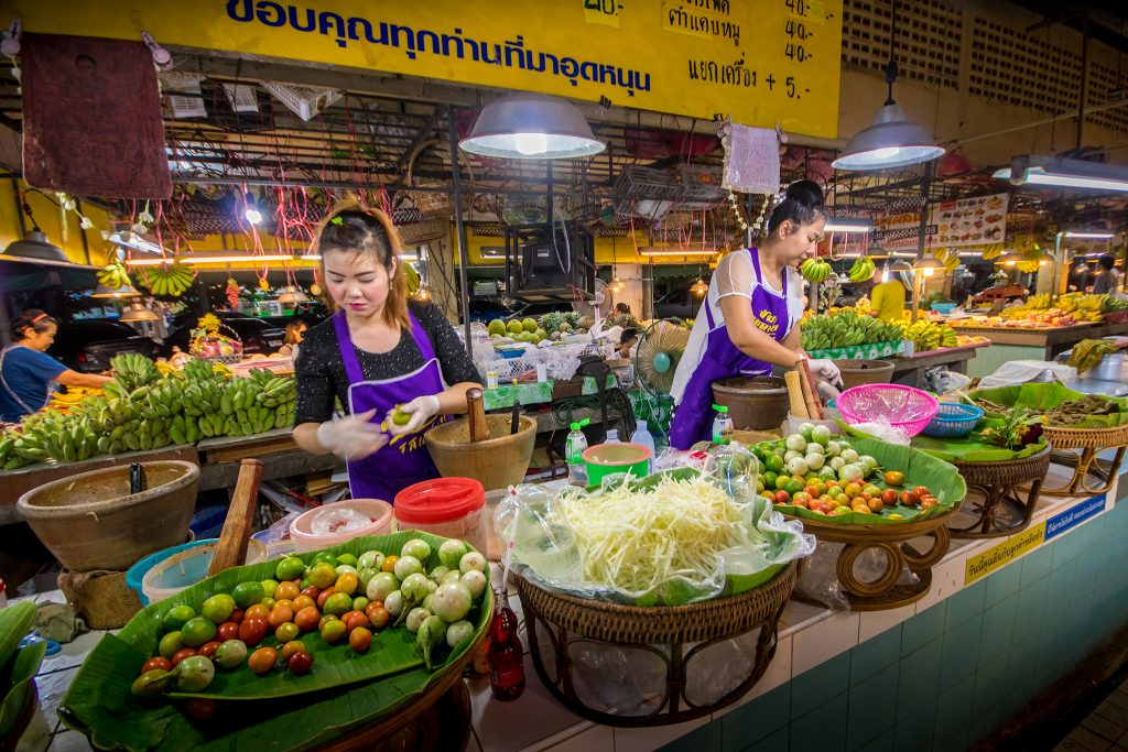 Two local women behind vegetable stands in market of Bangkok