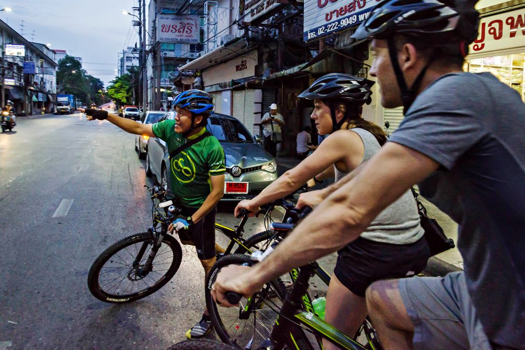 Guide pointing at something across the street and two tourists on bicycles in Bangkok