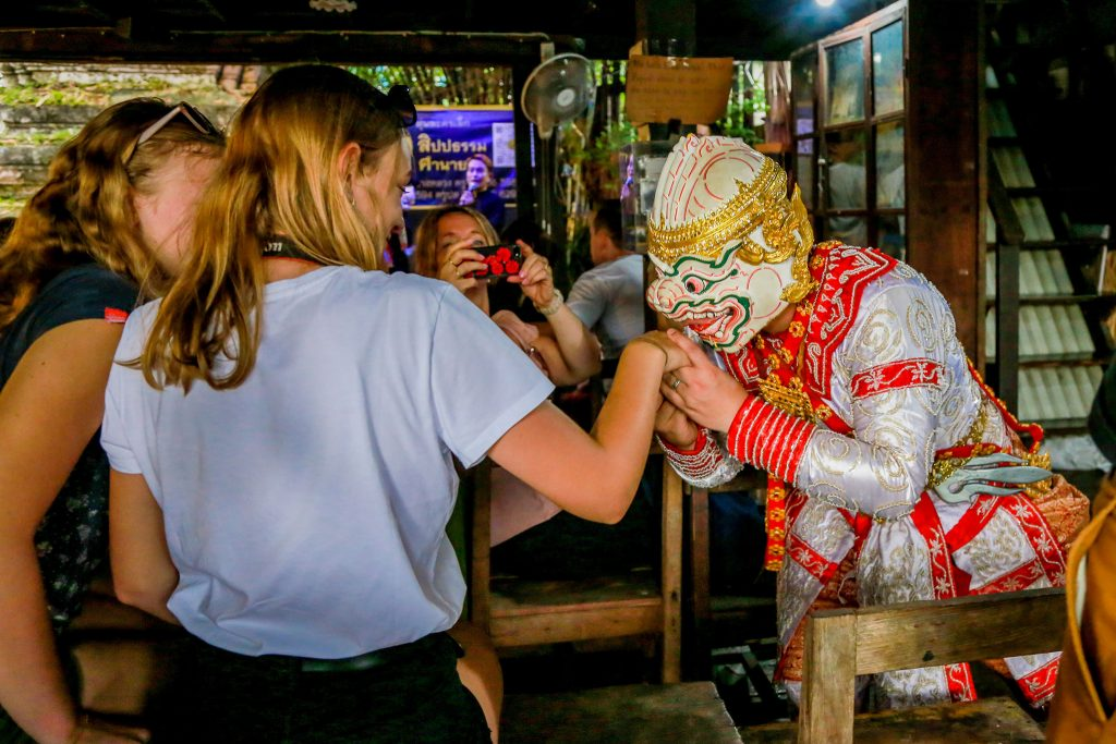 Thai person in outfit and mask kissing the hand of tourist girl at puppet show in Bangkok