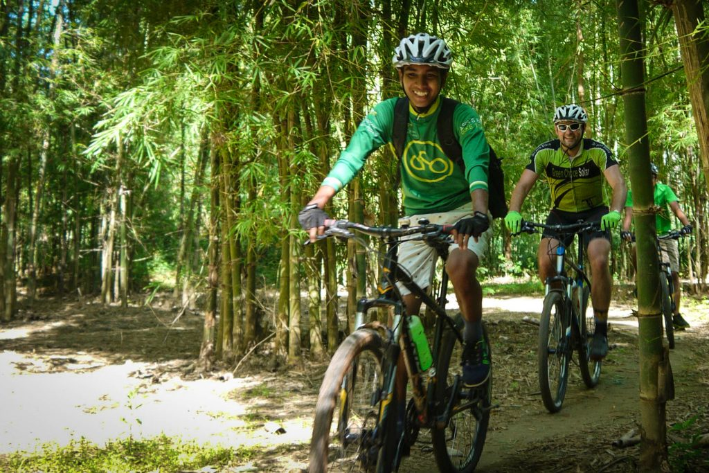 Mountain bikers on forest path near Inle Lake, Myanmar