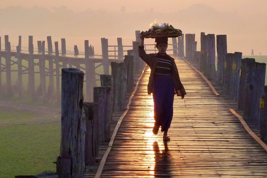 Woman balancing merchandise on head at twiligh on U-bein Bridge Myanmar