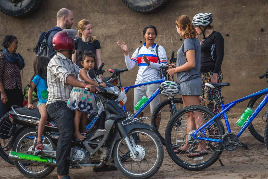 Guide talking to four cyclists with local man and two children on motorbike in front in Phnom Penh