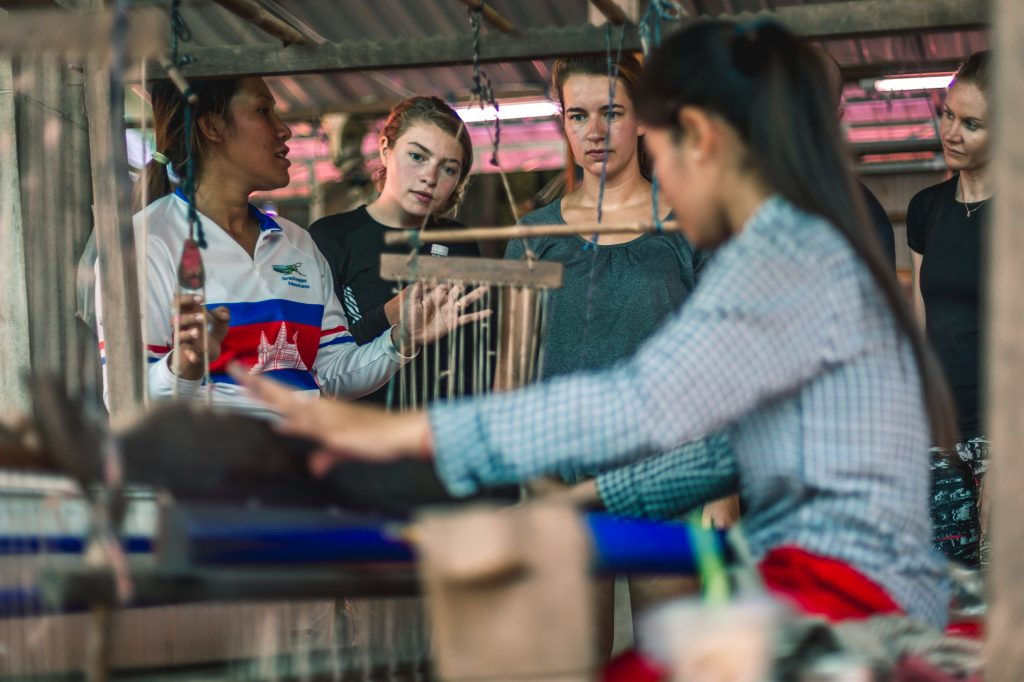 Guide talking to three tourists about local woman weaving on Silk Island of Phnom Penh