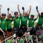 Seven cyclists with Grasshopper Adventures cycling jerseys on with hands in the air
