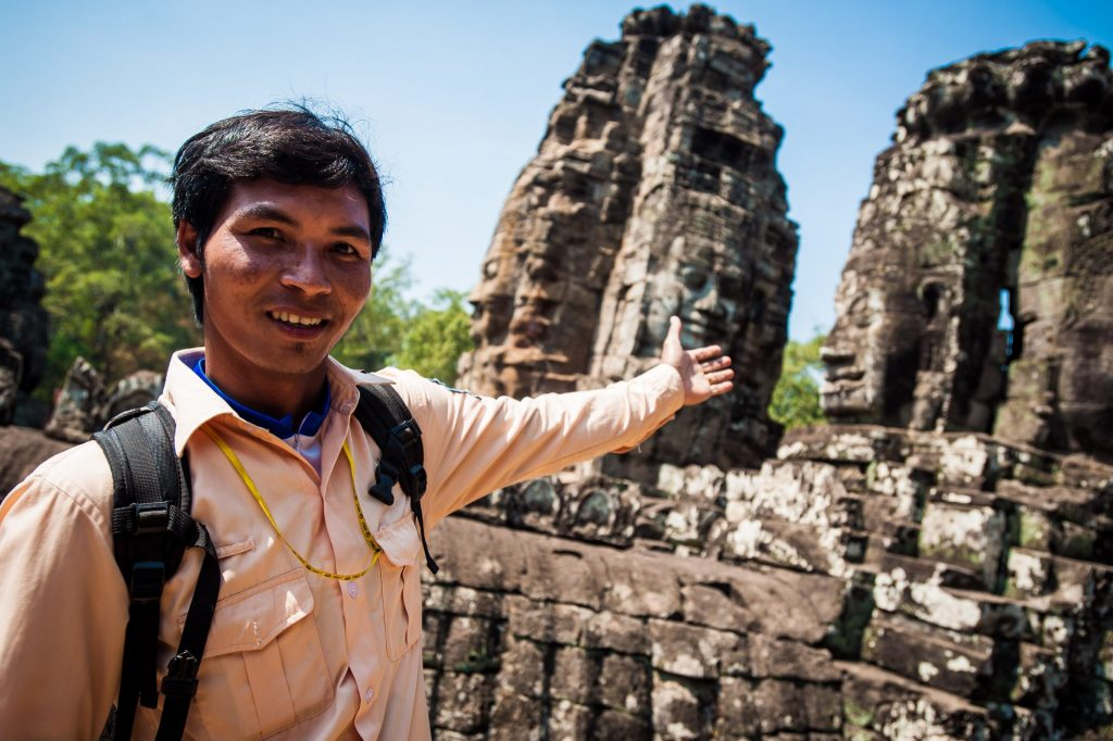 Local guide gesturing to the faces of Bayon temple