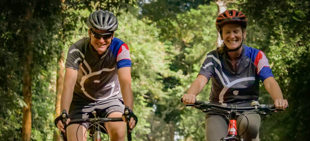 Two cyclists in helmets in jungle of Cambodia