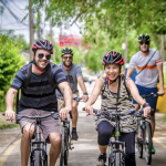 Four cyclists smiling while riding