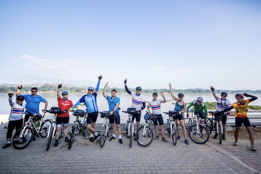 Eleven cyclists with arms in the air in front of water in Thailand