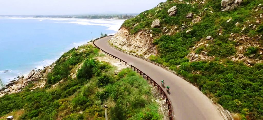 Winding paved road along ocean with two cyclists