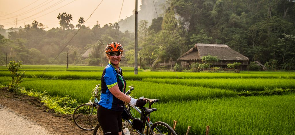 Smiling woman cyclist in rice paddies