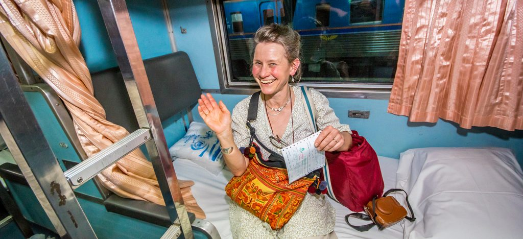 Smiling woman on sleeper train car