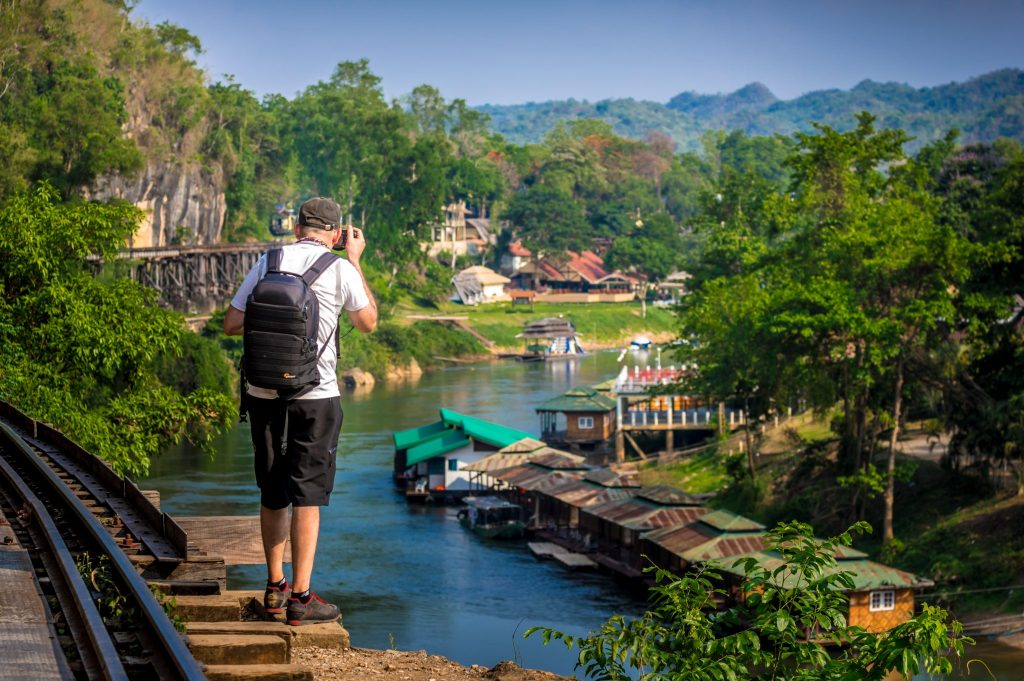 Man taking photo of River Kwai, floating houses, and railroad tracks
