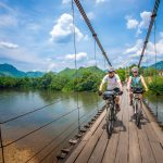Cyclists on a suspension bridge over the River Kwae