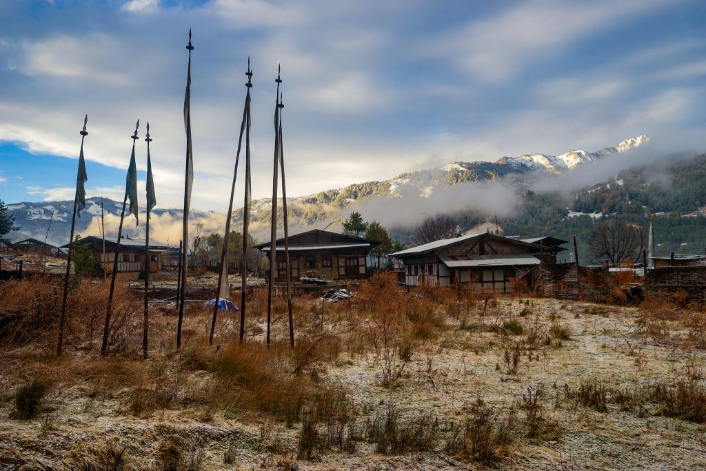 Buildings of Bumthang with brush in front and flags and misty mountains behind