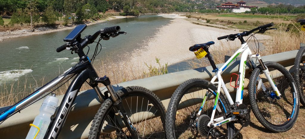 Two bicycles park on bridge with views of Bhutan behind