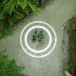 A pair of cyclists photographed from the top encircled by a GPS mark.