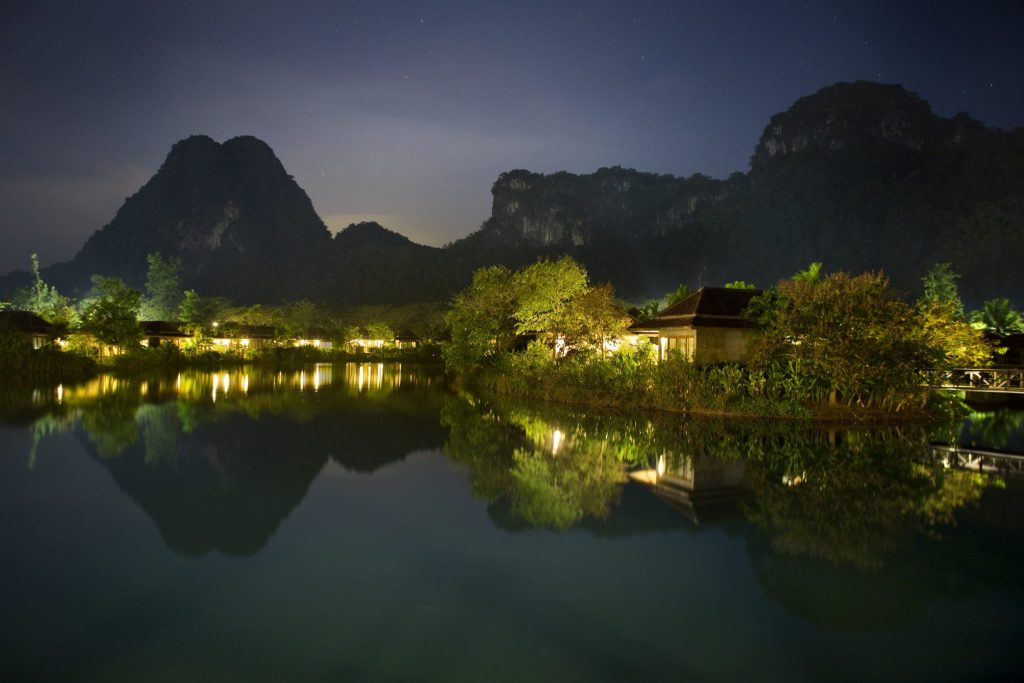 Luxury bungalows by a lake with a dramatic mountain backdrop in the Thailand peninsula.
