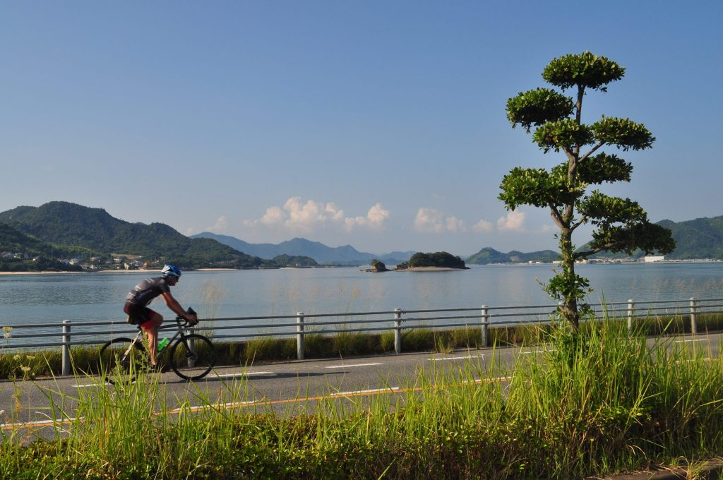 A cyclist on a tarmac road running alongside a lake with hilly landscape in the distance.